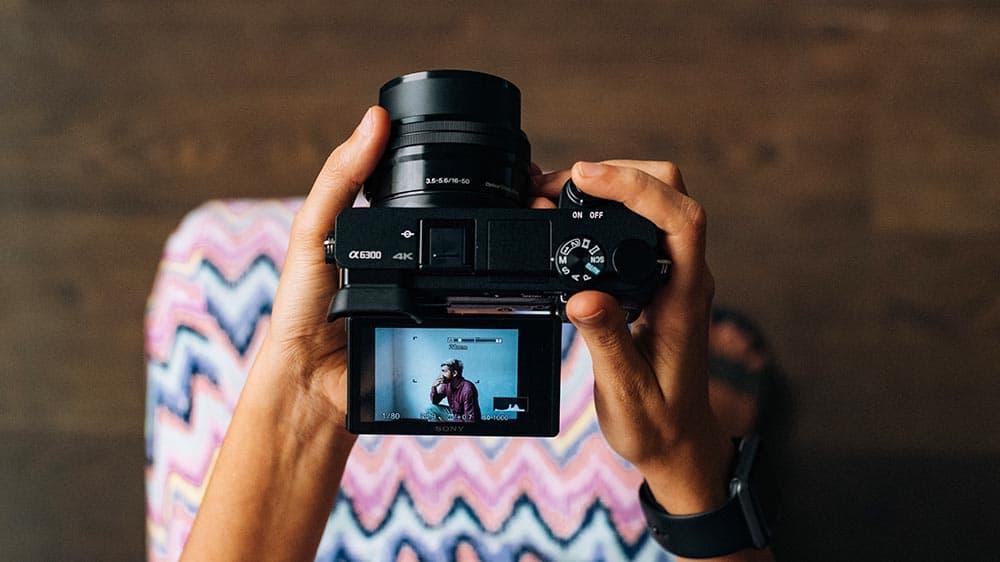 Vrouw maakt een portret van een man met een systeemcamera met een kantelbaar scherm