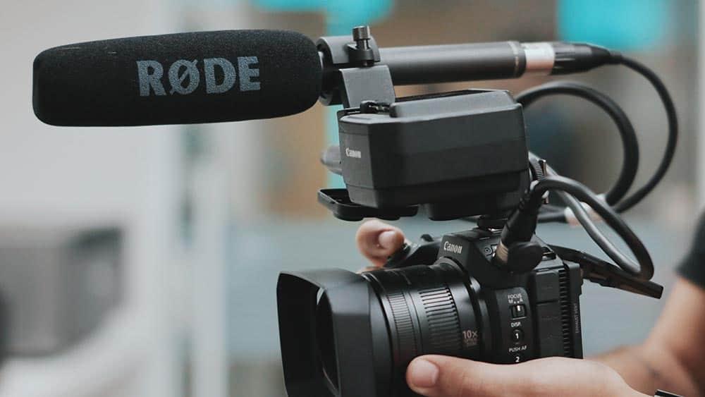 Persoon houdt systeemcamera met externe microfoon vast