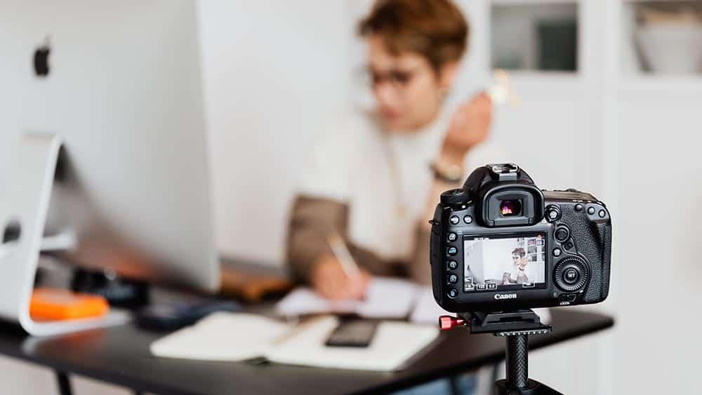 Canon spiegelreflexcamera op statief filmt persoon aan een bureau